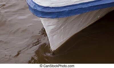 The water beats against the bow of the boat - Brown water...