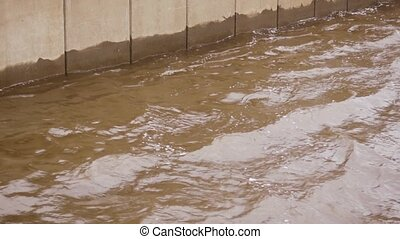 Water splashing about the concrete wall of the embankment or...