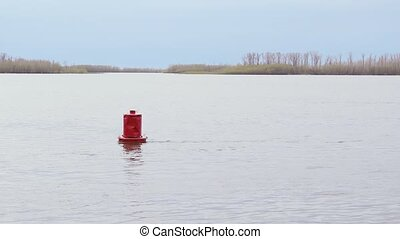 Red buoy on a white river in the distance spring forest