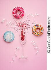 Flat lay of Celebration. Champagne glass with colorful party streamers and delicious donuts on pink background.