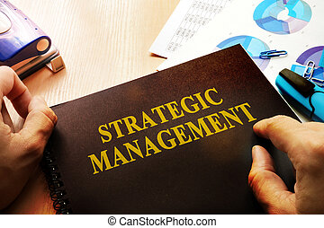 Hands holding documents with title Strategic management.