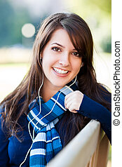 Mixed race college student listening to music - A portrait...