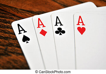Four Aces - Playing Cards on Wooden Table - A group of four...
