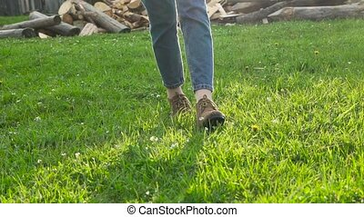 Girl walking on the green grass close-up