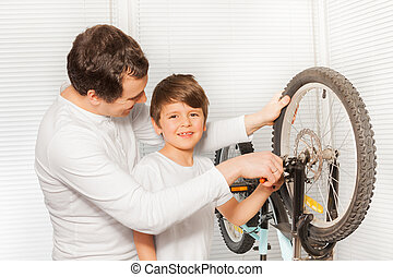 Boy helping his father repairing bicycle brakes