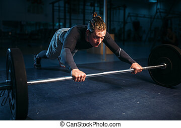 Strength athlete on training, pushups with barbell