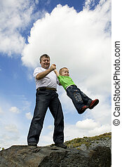 Father and his flying son Against the background sky and the...