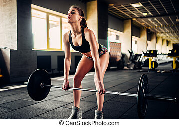 Female athlete training with barbell in sport gym
