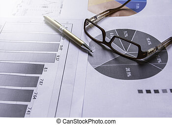 Pen with glasses on document for analyzing financial data and counting.