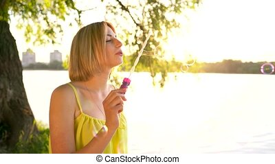 Young beautiful blonde blowing soap bubbles outdoors - Happy...