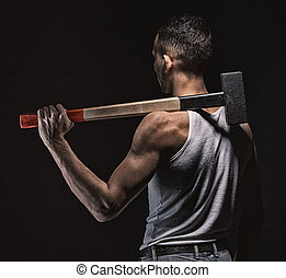 Muscular man with hammer from back