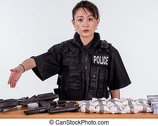 Female Asian police officer showing seized goods - Female...