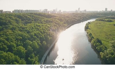 Aerial fly-over shot of the river and city park embankment...