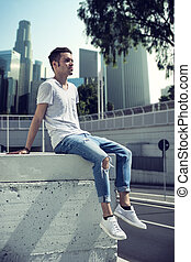 Attractive young man in city, sitting