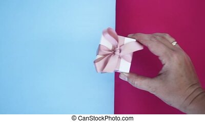 Box with pink ribbon - Someone hand placing gift box with...