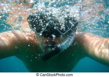 Diver in mask and snorkel under water. Close-up face.