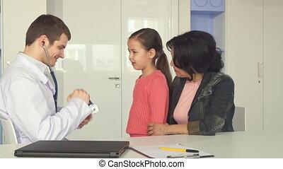 Doctor listens to the little girl's heartbeat - Brunette...