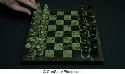 Knight's move in chess. Chess player makes a move the white knight forward pieces on the board. Man plays chess and makes clever cunning knight's move. Chessman playing chess