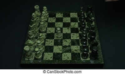 Two men playing chess. Chess game, chess players make a moves the black and white pawn forward