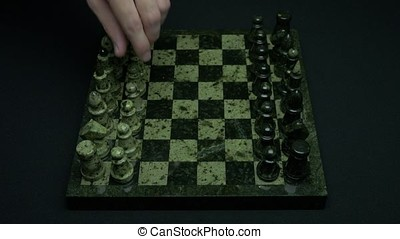 Man does first move in a chess game. Beginning of competition. The first step. hand chess and a chess board with chess pieces