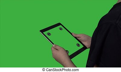Boy standing on green background with tablet