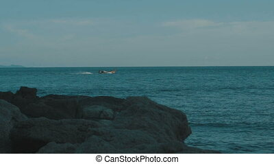Fishing boat on the sea - View from the beach on wooden...