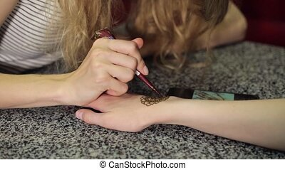 Woman making floral mehendi on a hand with henna on a table.