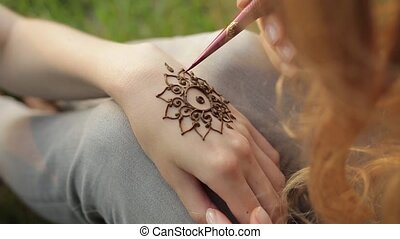 Young woman making floral mehendi on a hand using henna. -...