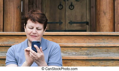 Elderly woman browsing mobile outdoors
