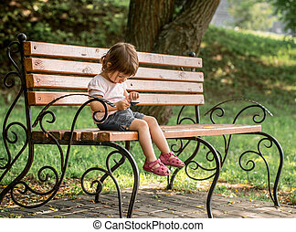 Little girl in the park on the bench with the phone - Little...