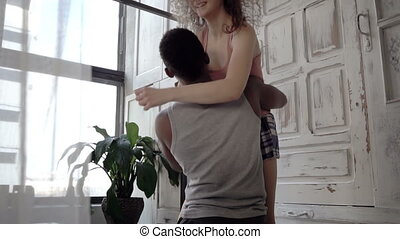 Happy multiethnic couple in pajamas. Woman jumps on man hands, falls on the bed. Male kisses female. Slow motion.