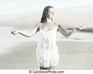 Rainy season - Beautiful woman near the stormy ocean at rain