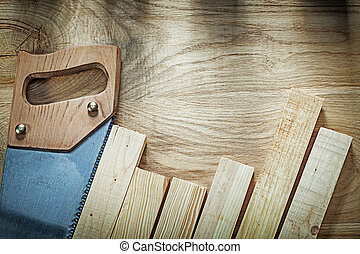 Composition of stainless hacksaw wooden planks on wood board...