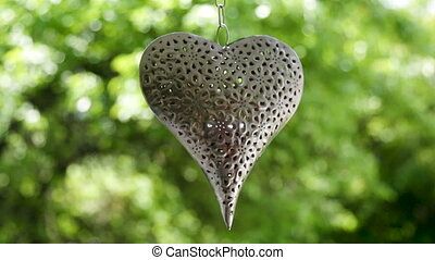iron heart hanging on a chain on a background of green trees...