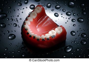 Dentures with braces waterdrops background , lower jaw