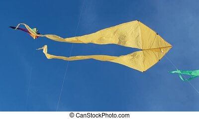 Yellow kite with two tails in flight against blue sky and sunny day