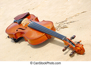 Violin - An old brown violin instrument lying in the sand of...