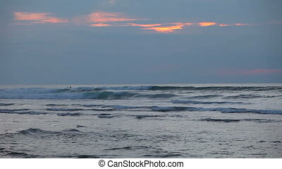 Ocean waves at sunset with surfers