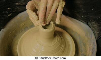 Professional male potter working in workshop, studio. Close...