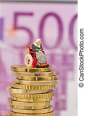 woman in wheelchair on money stack, symbol photo for...