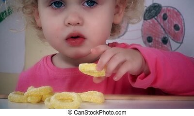 Adorable kid eating corn circle sticks. Dramatic color...