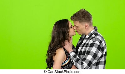 Loving couple look at each other and begin to kiss. Green...