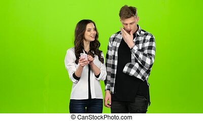 Loving guy and girl look in the phone and choose common...