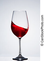 Wave of the red wine in the pure fragile wineglass standing...