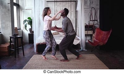 Young woman running through the room and jumping on man...