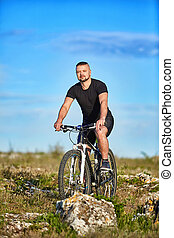 Young athlete cyclist riding mountain bike on rocky trail in the countryside.