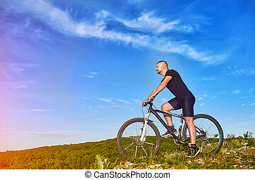 Young cyclist riding the bike on the beautiful summer mountain trail.