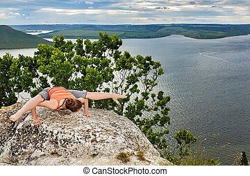Beautiful woman is practicing yoga on green mat on rock...