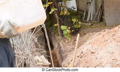 Man pouring water into trench with clayey soil for better...