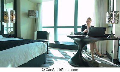 Sexy young blonde business woman works in the hotel room or office. Business trip
